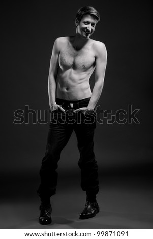 B&W full length portrait of a confident young man, on grey background - stock photo