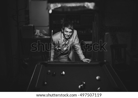 B&W Happy young groom playing billiard