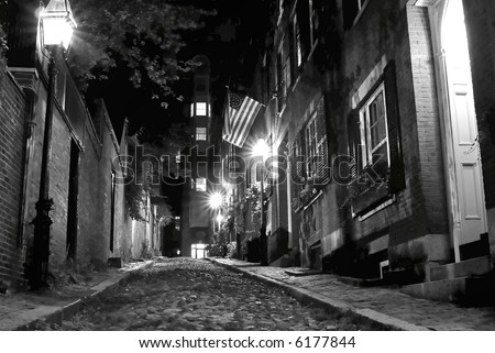 b/w night image of an old 19th Century cobble stone road in Boston Massachusetts, lit only by the gas lamps revealing the shuttered windows and brightly lit doorways of the rowhouses on Acorn Street