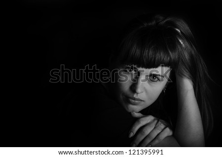 B / w portrait of a young beautiful woman on a black background