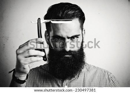 B/w portrait of bearded man with straight razor - stock photo