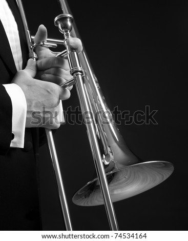 B&W slide trombone held next to a tuxedo clad torso, isolated on black. - stock photo