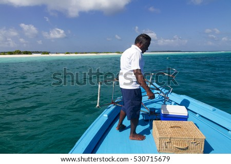 BAA ATOLL MALDIVES - CIRCA 2016 - An unidentified captain and crew anchor their traditional wooden boat on an uninhabited island.