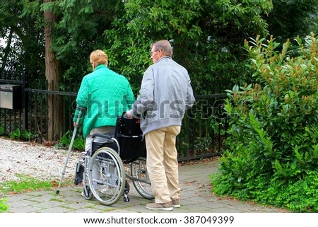 BAARN, NETHERLANDS - April 27. An elderly man is volunteer caregiver and helps his elderly wife to stand up from the weelchair on April 27, 2014 in Baarn.