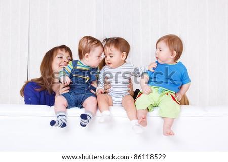 Babies communicating while sitting on sofa - stock photo