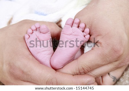 babies feet taken closeup in Father's hands - stock photo