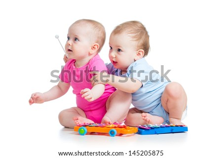 Babies girl and boy play musical toys. Isolated on white background - stock photo