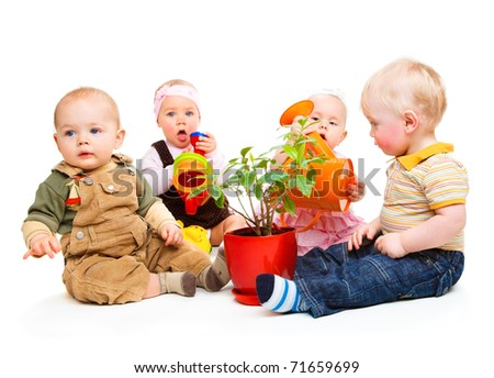 Babies group sitting around the potted plant - stock photo