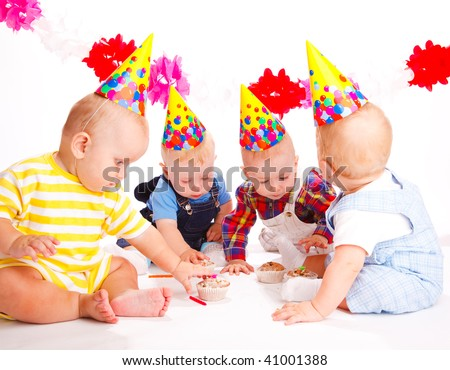 Babies in party hats celebrating first birthday - stock photo