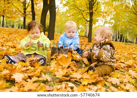 Babies playing with chestnuts in the autumn park - stock photo