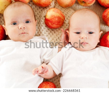 babies surrounded by apples - stock photo