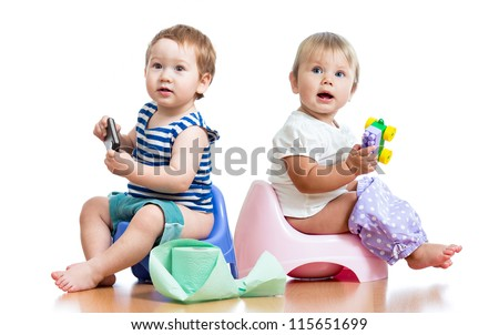 babies toddlers sitting on chamber pot and playing with toys - stock photo
