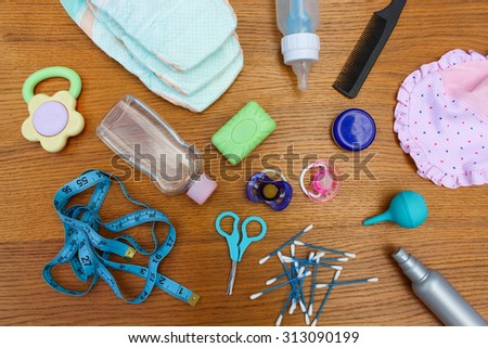 Baby accessories: pacifier, bottle, disposable diapers, scissors, funds for the bath, meter to measure the growth of the child, comb, oil for body, cotton swab  - stock photo
