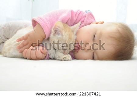 Baby and cat sleeping together on white sheet - stock photo