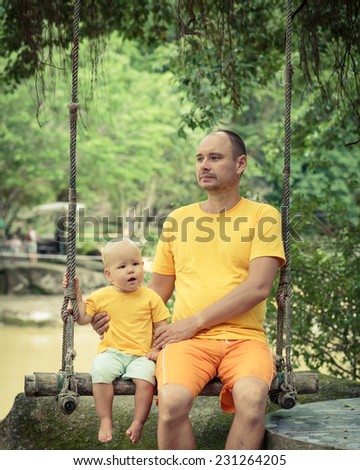 Baby and father are sitting on a swing - stock photo