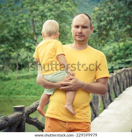 Baby and father on a bridge - stock photo