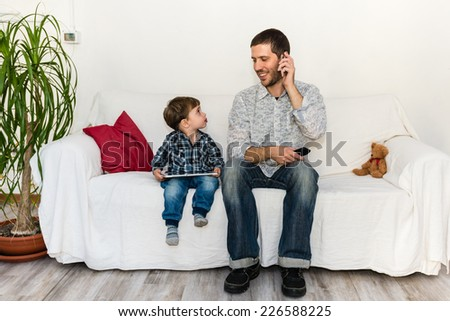 Baby and father playing with tablet and smiling themselves on a white sofa - stock photo