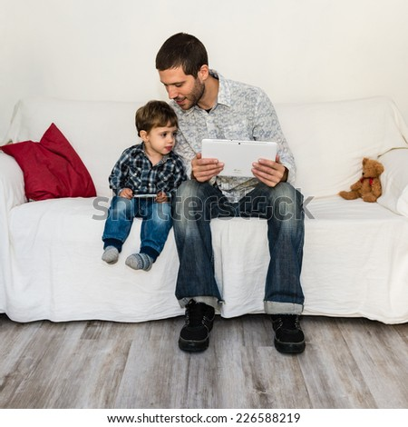Baby and father playing with tablet on a white sofa - stock photo