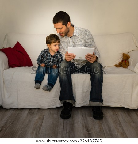 Baby and father playing with tablet on a white sofa both watching stuff of each other - stock photo