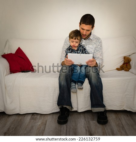 Baby and father playing with tablet on a white sofa with red pillow and little bear - stock photo