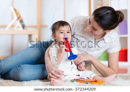 baby and her mother play musical toys - stock photo