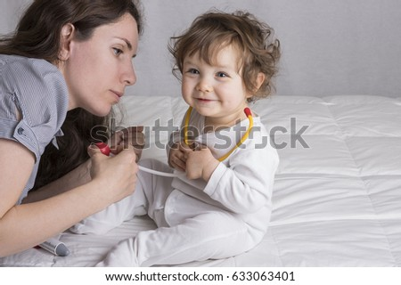 Baby and mom are playing with child doctor tools