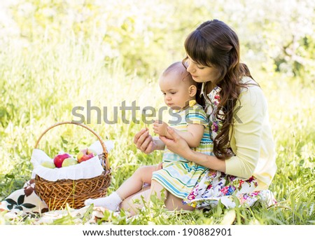 baby and mom sit with basket outdoors - stock photo