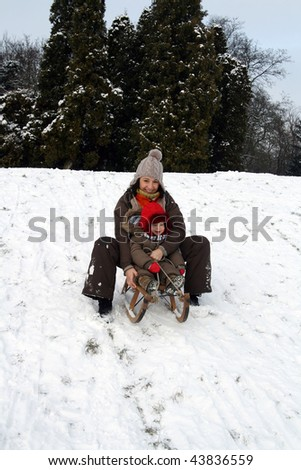 Baby and mom sledding in cold winter day - stock photo
