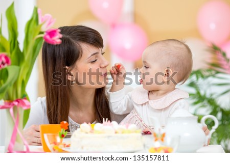 Baby and mother celebrate first birthday holiday - stock photo