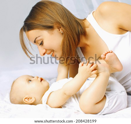 Baby and mother in bed - stock photo