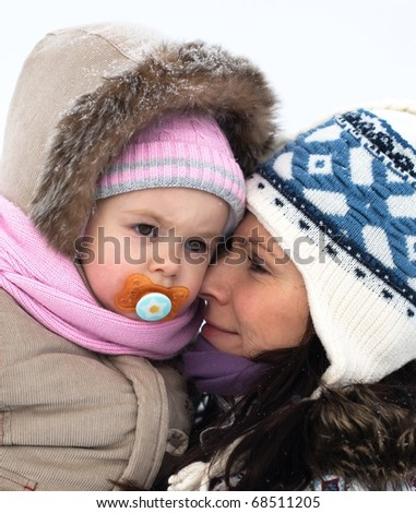 Baby and mother in cold winter day - stock photo