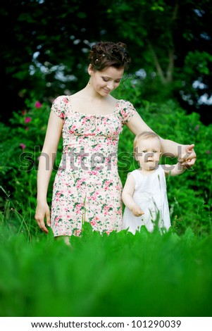 Baby and mother in  park - stock photo