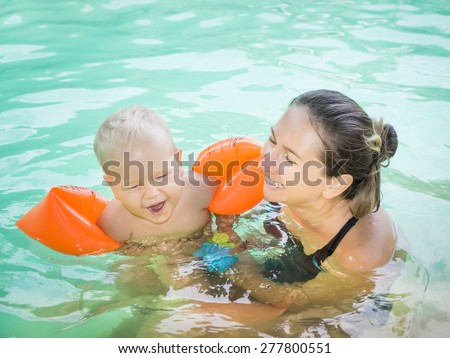 Baby and mother in swimming pool  - stock photo
