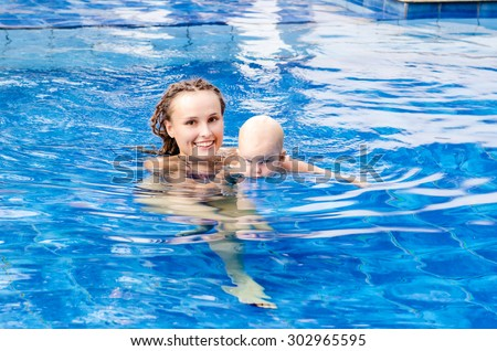 Baby and mother in the swimming pool - stock photo