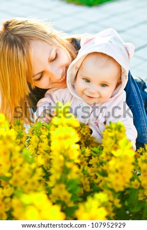 Baby and mother looking on yellow flowers with curiosity - stock photo