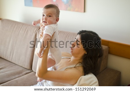 Baby and mother on sofa. Diapers need a change. - stock photo