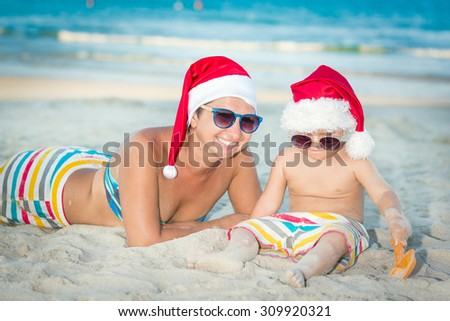 Baby and mother on the beach. Christmas concept - stock photo