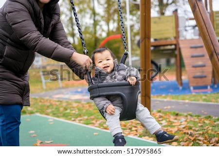 Baby and mother play swing in the park