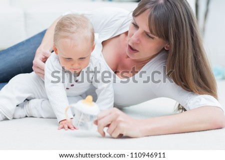 Baby and mother sitting on the floor in living room - stock photo
