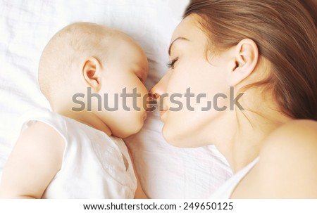 Baby and mother sleeping together on the bed - stock photo
