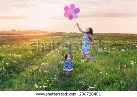 baby and mother with balloons outdoor - stock photo