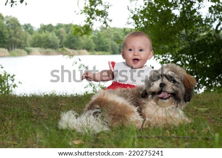 Baby and puppy are playing near the lake - stock photo