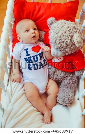 Baby and teddy bear in a cradle