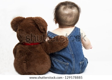 Baby and Teddy Bear sitting with backs to us - concept best friends - stock photo