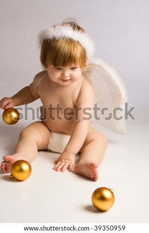 Baby angel playing with golden Christmas decoration - stock photo
