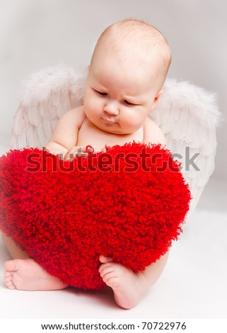 Baby angel playing with red heart, over gray - stock photo