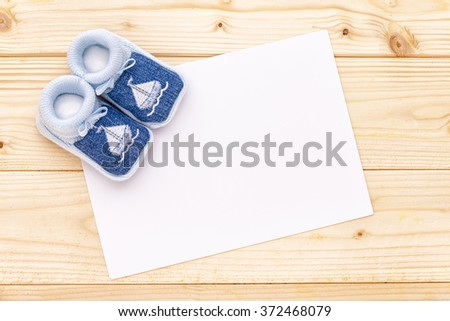 Baby announcement card with baby blue shoes on pine wood background. - stock photo