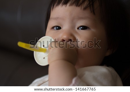 baby asian girl sucking on pacifier  - stock photo