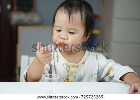 Baby asian toddler girl feeding medicine by themself