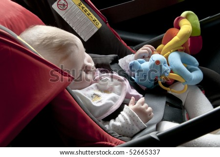 baby asleep in the car, in a safety seat - stock photo